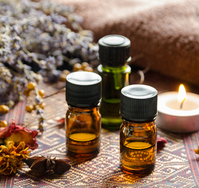 essential oils with candle and herbs